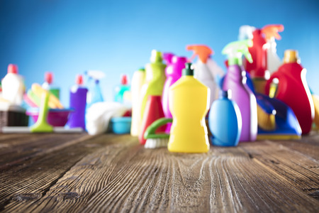 Spring cleanup theme. Variety of colorful house cleaning products on a rustic wooden table and blue background. Banque d'images