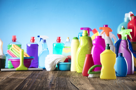 Spring cleanup theme. Variety of colorful house cleaning products on a rustic wooden table and blue background. Imagens