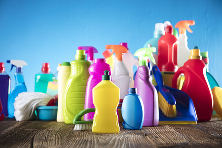 office cleanup: Spring cleanup theme. Variety of colorful house cleaning products on a rustic wooden table and blue background. Stock Photo