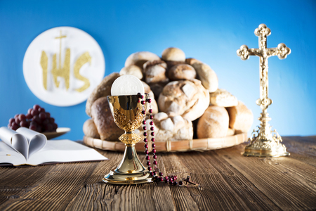 tabernacle: First Holy Communion. Catholic religion theme. Crucifix, Bible, bread on rustic wooden table and blue background.