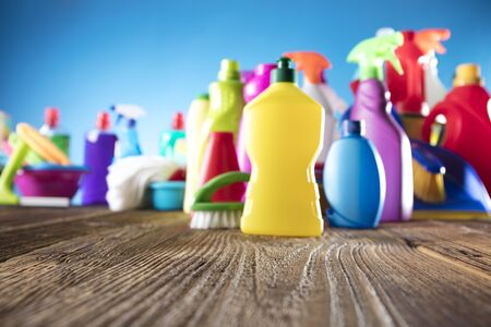 Spring cleanup theme. Variety of colorful house cleaning products on a rustic wooden table and blue background. Archivio Fotografico