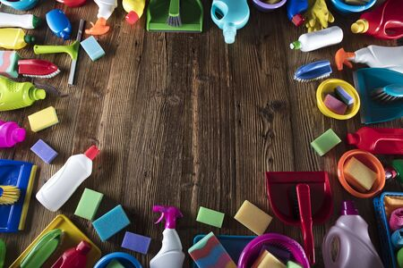 Spring cleanup theme. Variety of colorful house cleaning products on a rustic wooden table. Top view. Banque d'images