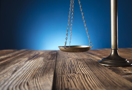 jurado: Scale of justice on old wooden table and blue background.  Law theme and concept.