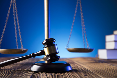 Gavel of the jugde and scale of justice on old wooden table and blue background.  Law theme and concept.