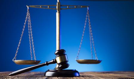 Gavel del jugde y la escala de la justicia en la vieja mesa de madera y el fondo azul. Tema y concepto de ley. Foto de archivo - 77359027