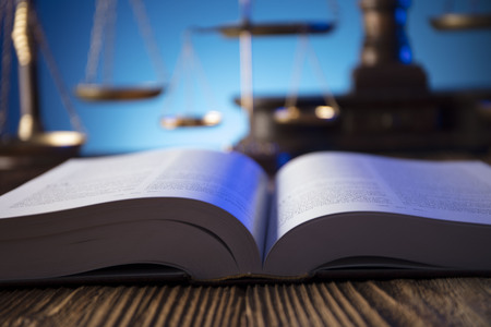 Lawyer, counselor office. Consultation with a lawyer concept. Gavel of the jugde and scale of justice on old wooden table and blue background. Archivio Fotografico