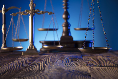 Lawyer, counselor office. Consultation with a lawyer concept.  Scale of justice on old wooden table and blue background.