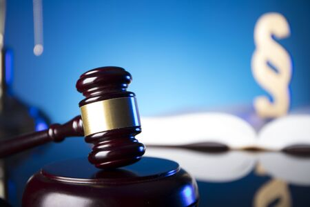 Lawyer, counselor office. Consultation with a lawyer concept. Gavel of the jugde and scale of justice on glass table and blue background. Stock Photo