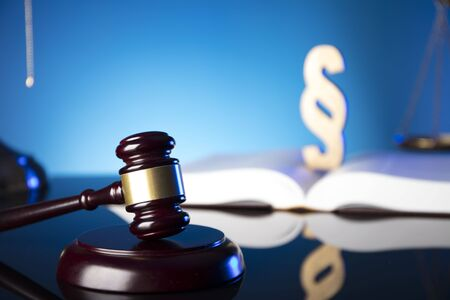 Lawyer, counselor office. Consultation with a lawyer concept. Gavel of the jugde and scale of justice on glass table and blue background. Archivio Fotografico