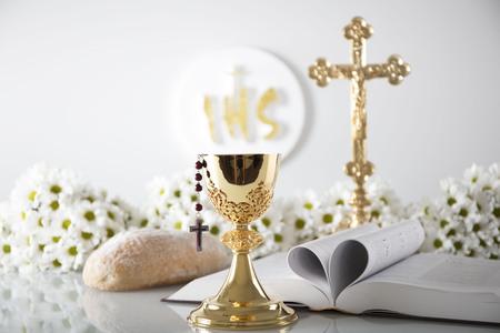 Pierwsza Komunia Święta. Motyw religii katolickiej. Krucyfiks, Biblia, chleb samodzielnie na biały tabeli i białe tło. Zdjęcie Seryjne
