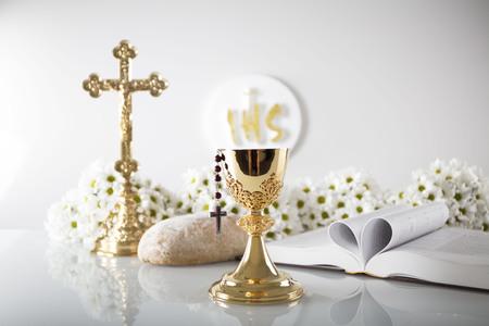 Prima Comunione. Tema della religione cattolica. Crocifisso, Bibbia, pane isolato su bianco tavolo e sfondo bianco. Archivio Fotografico - 78979248