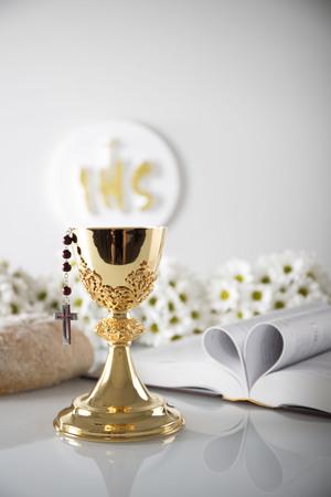 Primera comunión. Tema de la religión católica. Crucifijo, Biblia, pan aislado en la mesa blanca y fondo blanco.