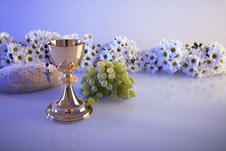 Eerste Heilige Communie. Thema van de katholieke religie. Crucifix, Bijbel, brood op witte lijst en witte achtergrond wordt geïsoleerd die. Stockfoto