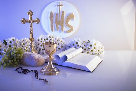 첫 번째 성만찬. 가톨릭 종교 주제. 십자가, 성경, 흰색 테이블 및 흰색 배경에 고립 된 빵. 스톡 콘텐츠