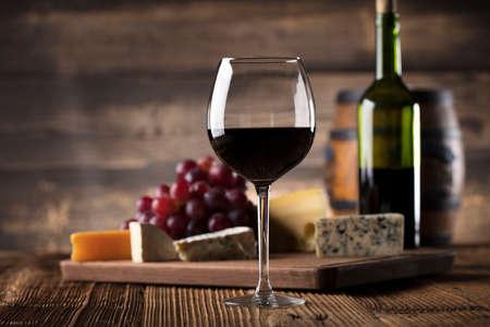 赤ワイン、チーズ、古い木製のテーブルのブドウのガラス。古い木製の背景。 写真素材
