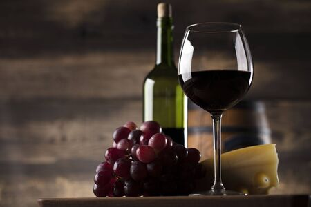 tabla de quesos: Glass of red wine, cheese and grapes on old wooden table. Old wooden background.