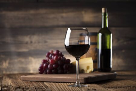 degustation: Glass of red wine, cheese and grapes on old wooden table. Old wooden background.7