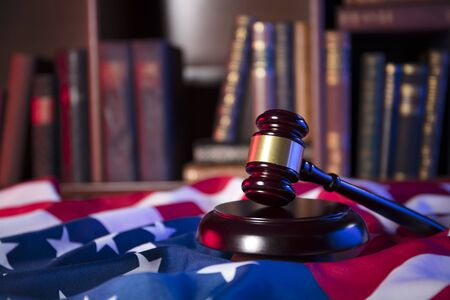 Independence Day theme. 4th of July. American Declaration of Independence. Gavel, library, books, codes. American flag. Stock Photo