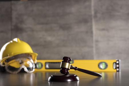 Derecho de la construcción. Casco y martillo. Mesa de piedra. Foto de archivo - 83074072