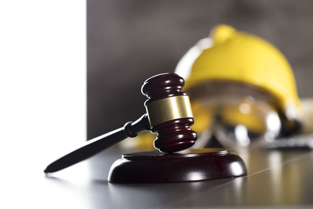 Derecho de la construcción. Casco y martillo. Mesa de piedra. Foto de archivo - 83074048