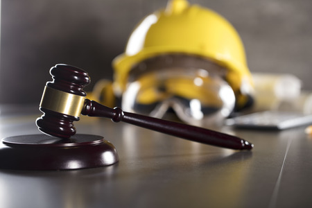 Construction law. Helmet and gavel. Stone table.