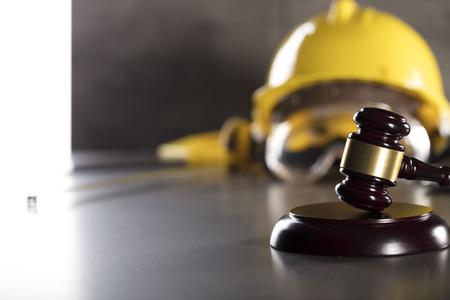 Derecho de la construcción. Casco y martillo. Mesa de piedra. Foto de archivo - 83074036
