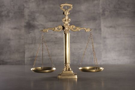 Judge concept. Golden scale of justice.  Gray stone background. Place for typography.