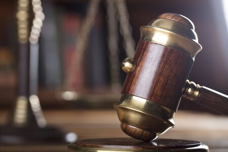 scale of justice: Law concept. Gavel on wooden table and brown background.