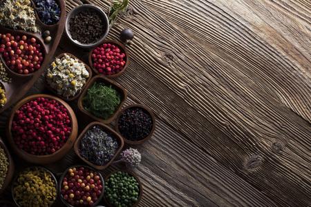 自然医学。焦点深度が浅い。木製のテーブル。ボウルにハーブ、ベリーや花