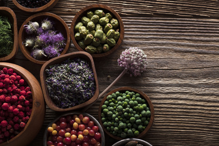 Natural medicine. Shallow depth of focus. Wooden table. Herbs, berries and flowers in bowls