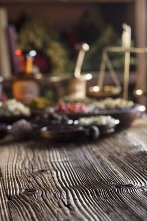 Alternative medicine. Wooden table, shallow depth of focus. Mortar, berries, flowers and herbs assorted in bowls.