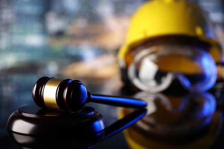 Law theme. Construction law's symbols  - helmet and gavel. Archivio Fotografico