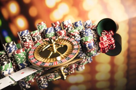Casino thme. High contrast image of casino roulette, poker game, dice game, poker chips on a gaming table, all on colorful bokeh background. Stock Photo