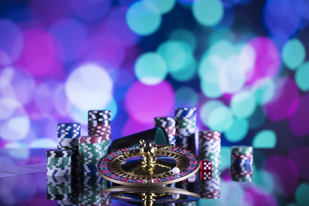 Roulette, chips, cards and dice on colorful bokeh.