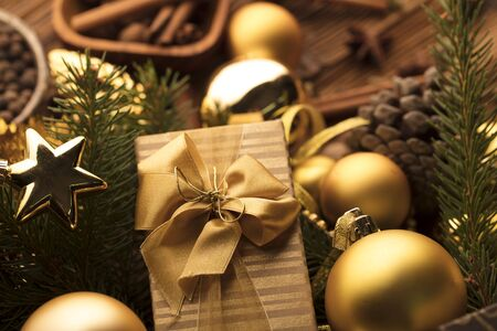 Christmas decoration in golden and brownish aesthetics with presents in boxes, golden baubles, christmas spices all on a rustic wooden background with copy space.