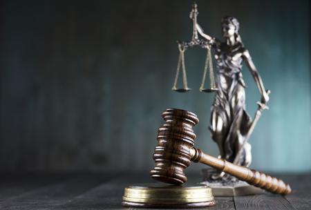 Consulta con un concepto de abogado. Estatua de la justicia, mazo en fondo verde.