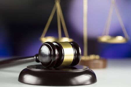 Gavel and scales on bokeh background. Stock Photo