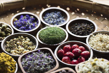 Natural medicine.  Herbs, berries and flowers in bowls on wooden table. Imagens - 88291520