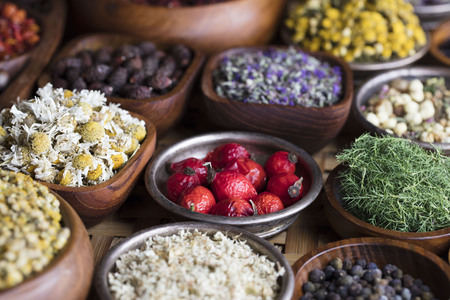 Natural medicine.  Herbs, berries and flowers in bowls on wooden table.