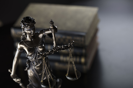 Law theme. Judge concept. Statue of justice and books in old court library. Stock Photo