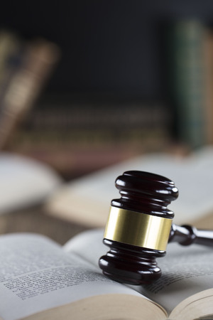 Judge concept. Mallet of the judge and books on wooden desk. Stock Photo