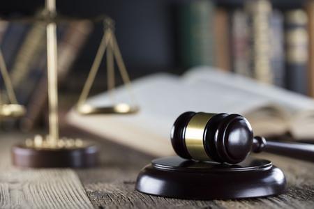 Sędzia koncepcji. Młotek sędziego, skala sprawiedliwości i książki na drewnianym biurku.
