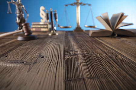Judge concept. Mallet of the judge, justice scale and books on wooden desk and blue background. Stockfoto