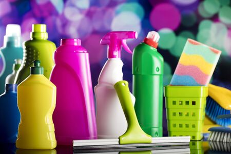 Cleaning products on colorful bokeh background and glass table.