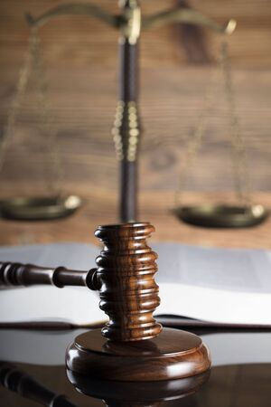 Scale, gavel and books on a wooden background.