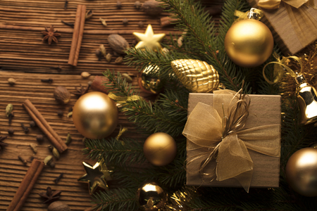 Christmas decoration concept. Golden baubles and  Christmas spices all on a rustic wooden background with copy space.