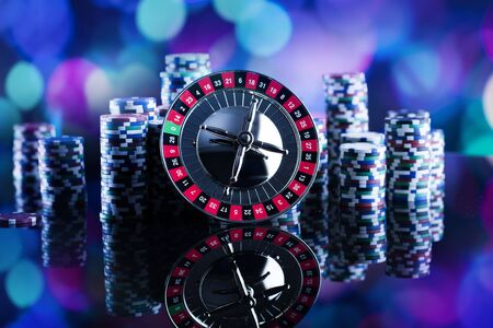 Casino thema. Hoog contrastbeeld van casinoroulette, pookspel, dobbelspel, pookspaanders op een gokkenlijst, allen op kleurrijke bokehachtergrond. Plaats voor typografie en logo. Stockfoto