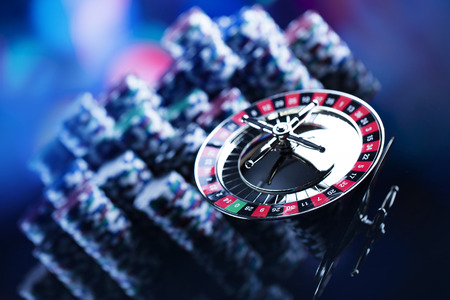 Casino theme. High contrast image of casino roulette, poker game, dice game, poker chips on a gaming table, all on colorful bokeh background. Place for typography and logo. Stockfoto