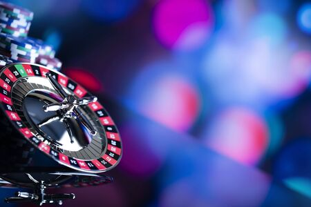 Casino theme. High contrast image of casino roulette, poker game, dice game, poker chips on a gaming table, all on colorful bokeh background. Place for typography and logo. Stock Photo