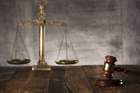 Judge antique gavel. Law symbols. Legal office. Wooden rustic table and stone background. Foto de archivo